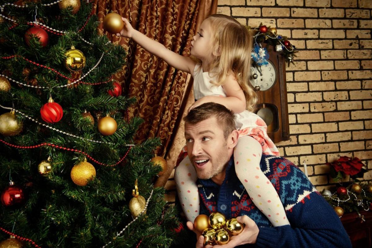ребенок украшает елку с папой